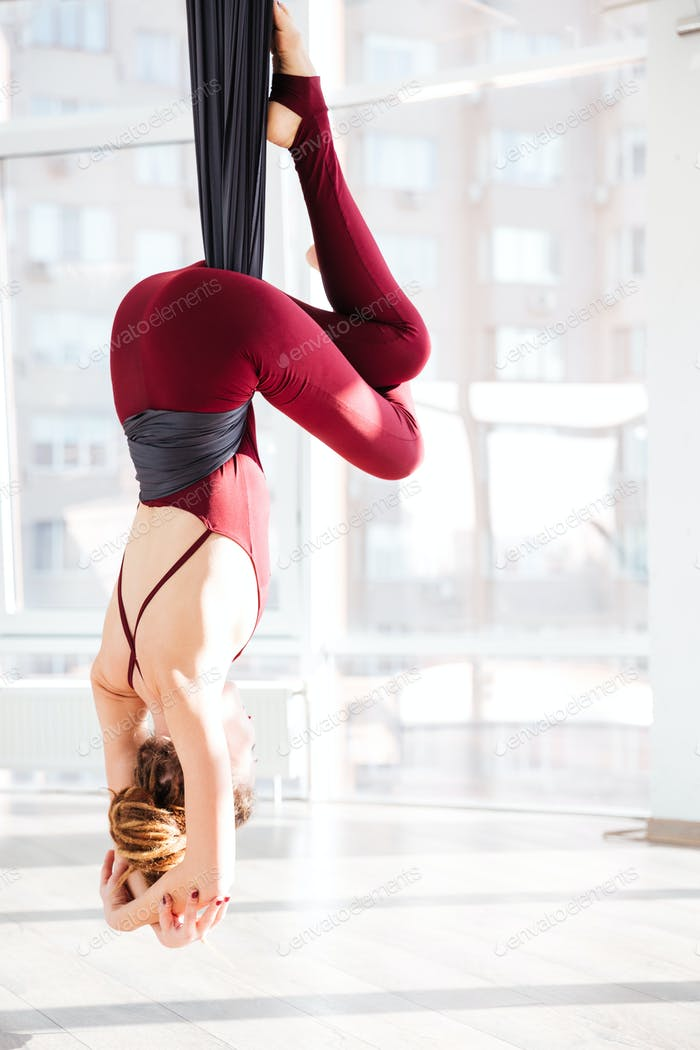 Young woman practicing antigravity yoga exercises in studio