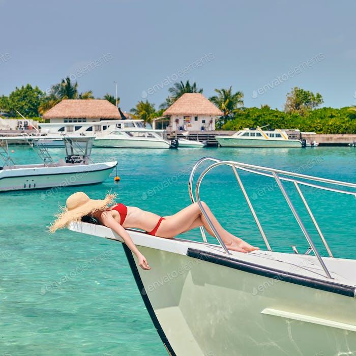 Woman in red bikini lying on boat bow