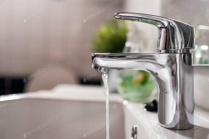 Agua fría que fluye del grifo en el baño limpio y brillante