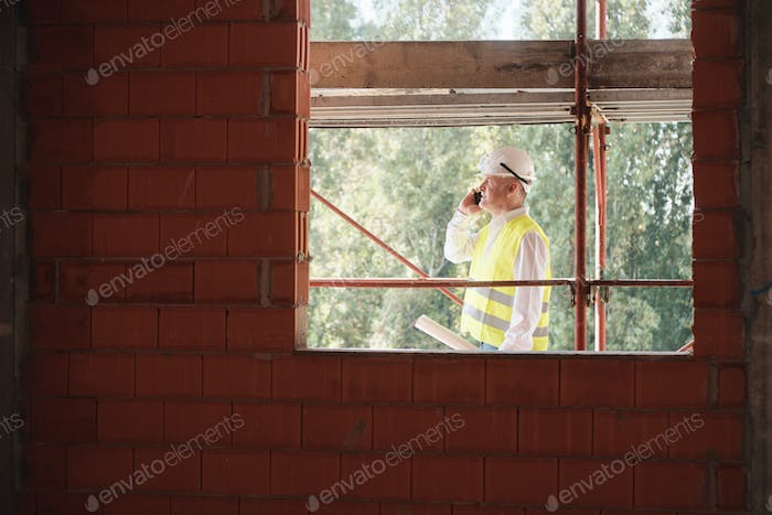 Engineer Talking On Mobile Phone In Construction Site