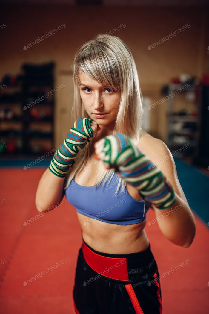Female kickboxer in boxing bandages and sportswear