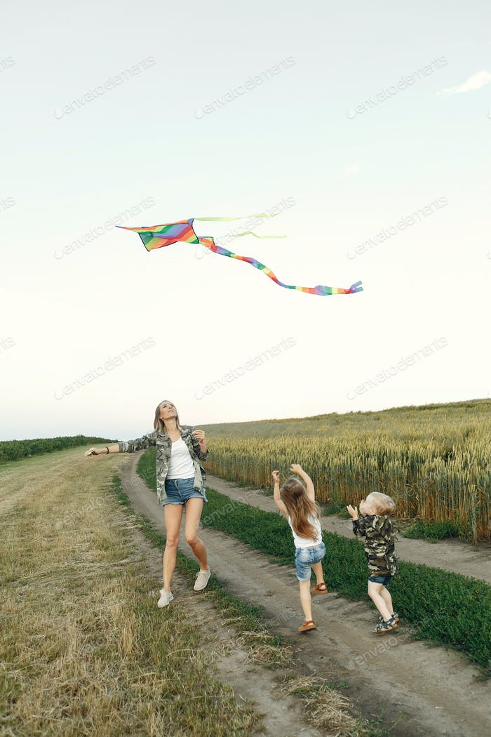 Mother with cute little children in a summer field