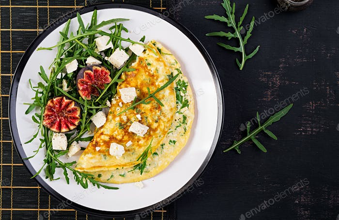 Omelette with feta cheese, parsley and salad with figs, arugula on white plate.