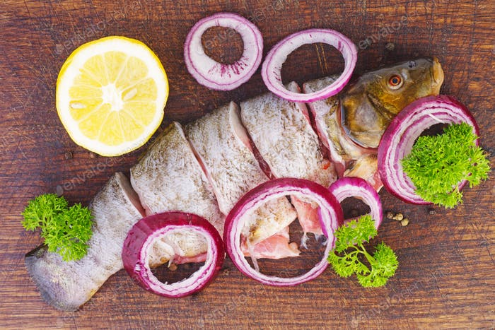 Sliced ready-to-cook tench fish with parsley, onions and lemon