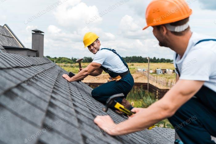 selective focus of happy repairman looking at coworker on roof