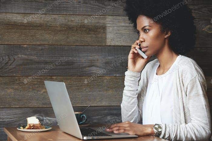 Concepto de tecnología y comunicación. Exitosa empresaria afroamericana con peinado afro