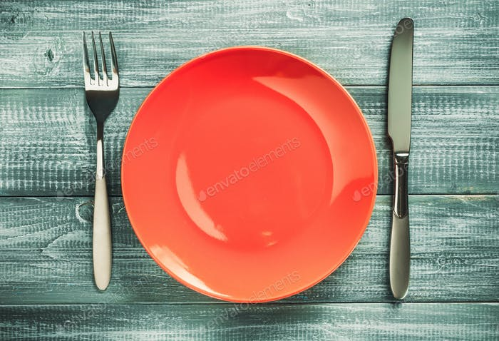 plate, knife and fork on wood