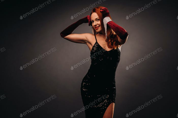 Red-haired girl in a black dress and elegant gloves on a black background