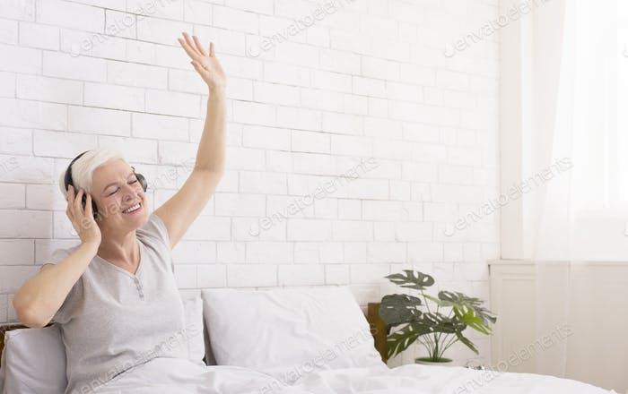 Playful senior lady in headphones listening to music in bed