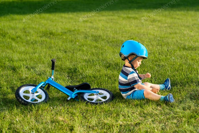 Boy in helmet sitting on grass with blue balance bike
