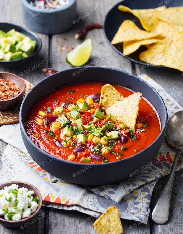 Mexican Tomato, Bean, Bell Pepper Soup in Black Bowl with Nachos Chips. Wooden Background