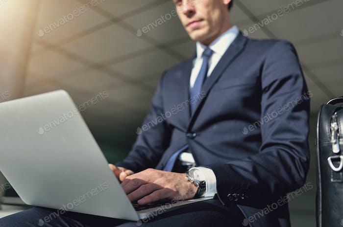 Selbstbewusster Geschäftsmann arbeitet mit seinem grauen Notebook