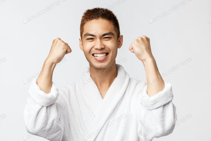 Beauty, spa and leisure concept. Satisfied asian man in bathrobe fist pump delighted, smiling