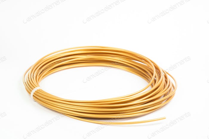 Top view of golden rolled filament plastic for 3D Printing Pen isolated on white