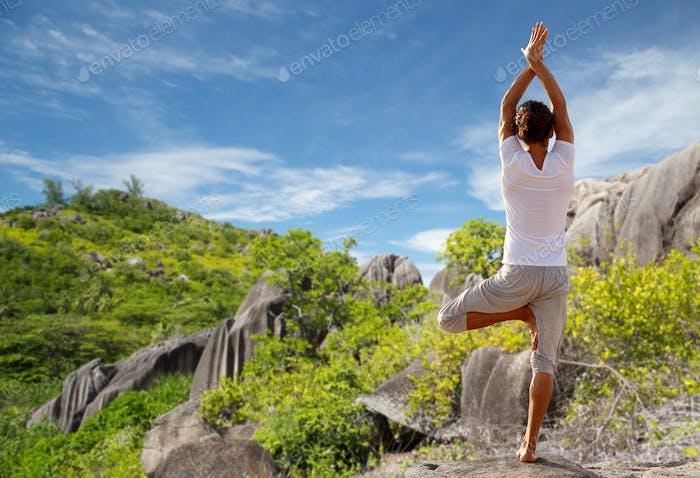 junger Mann machen Yoga-Baum Pose im freien