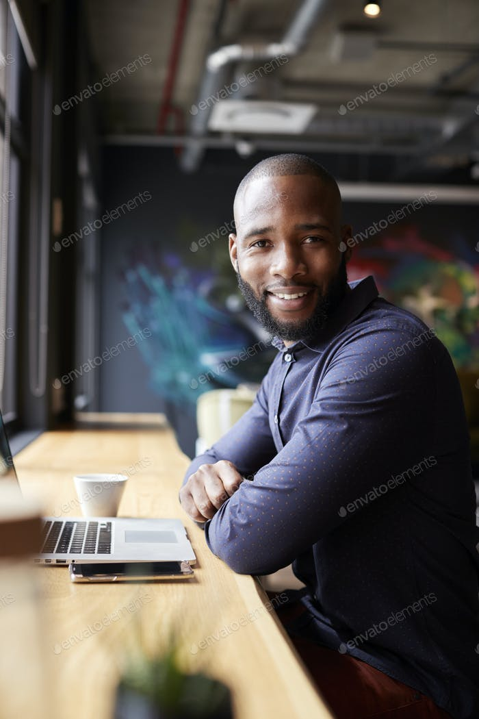 Black male creative sitting by window in cafe using laptop, turning and smiling to camera, vertical