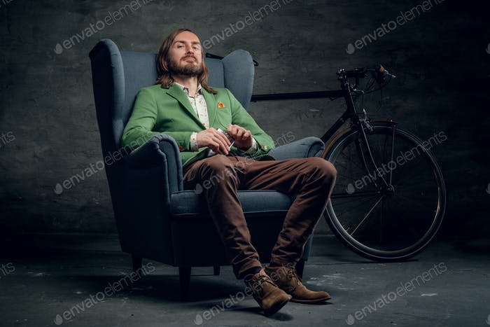 A man sits on a chair with bicycle on background.