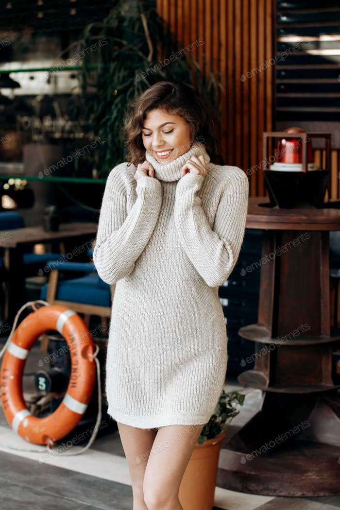 Young charming girl dressed in beige knit dress poses in the street