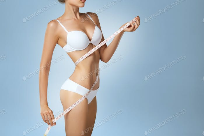 Slim tanned woman with measure tape around waist