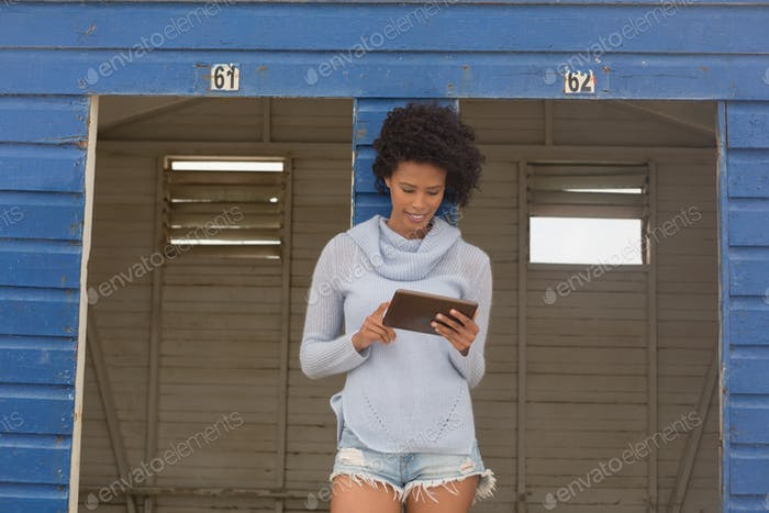 Woman using digital tablet standing at beach hut