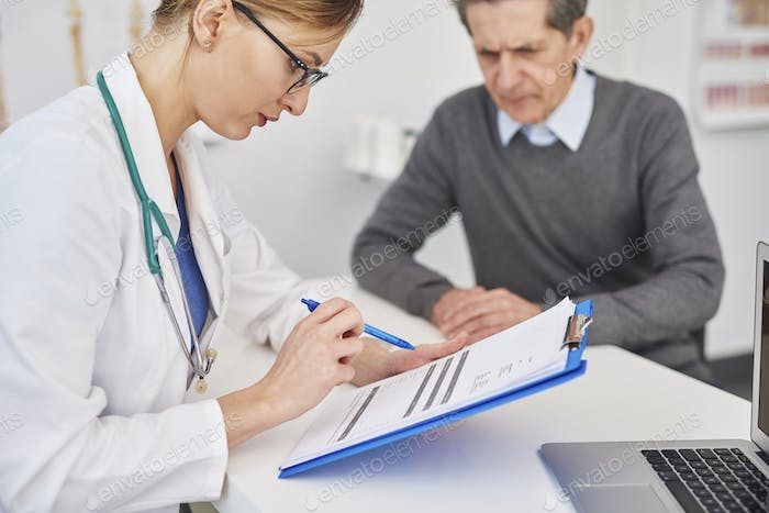 Doctor looking at results on the clipboard