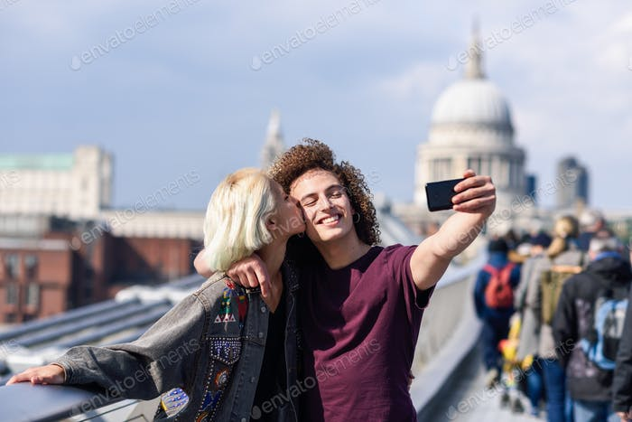 Happy couple taking a selfie photograph on London's Millennium Bridge