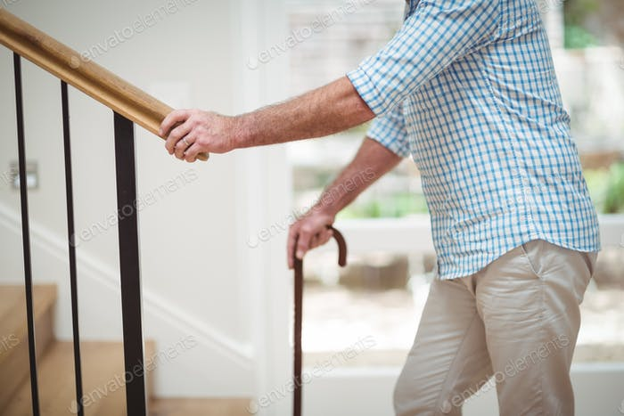 Senior man climbing upstairs with walking stick