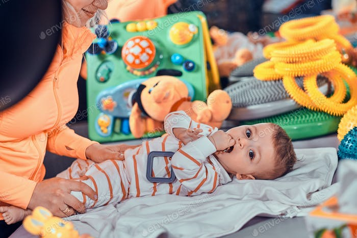 Happy smiling cute baby is lying on the special table surrounded by ortopedic toys