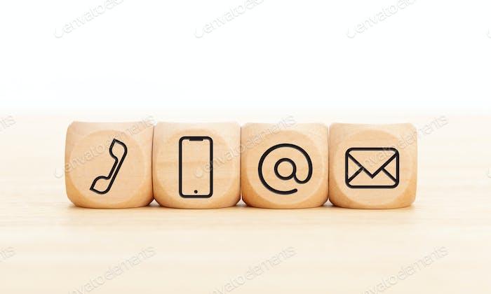 Kontaktieren Sie uns Icons in Holzklötzen auf Holztisch