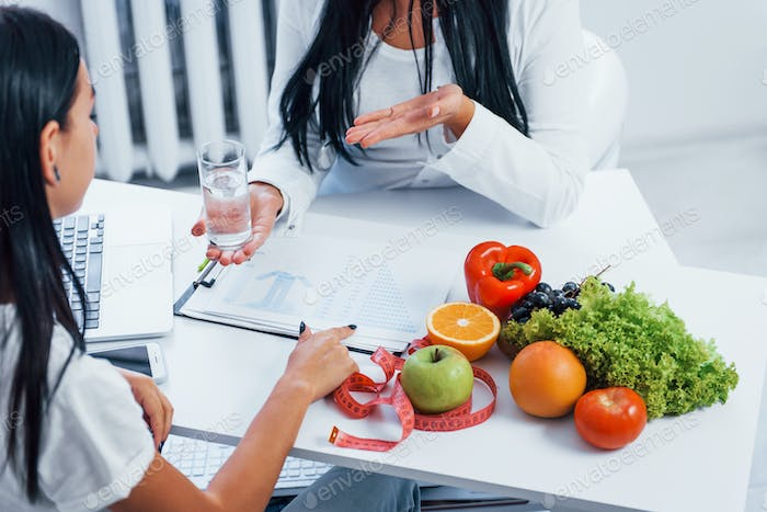 Female nutritionist gives consultation to patient indoors in the office