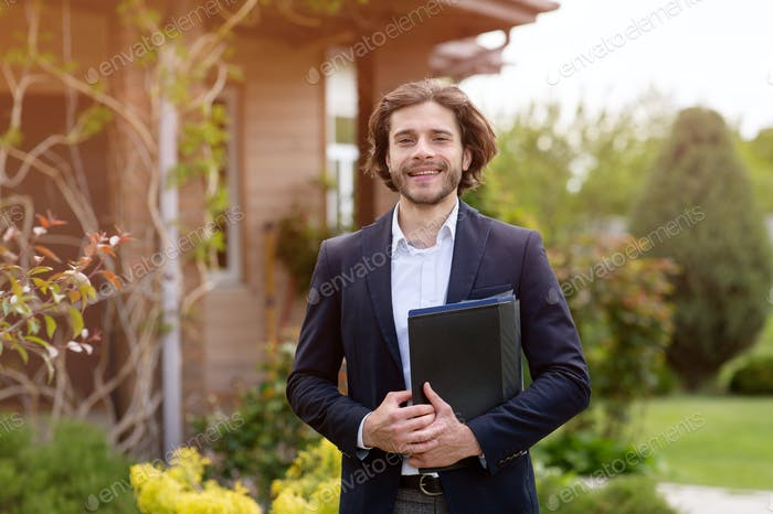 Portrait of happy real estate agent with documents posing near house outdoors