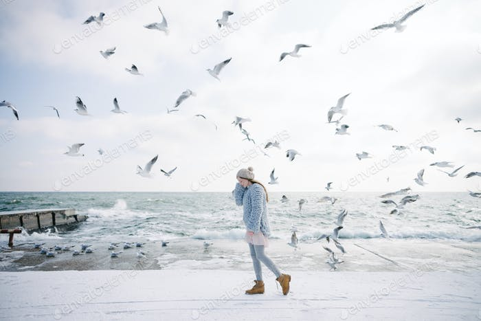 Stylish Young Girl on Winter Seashore With Seagulls