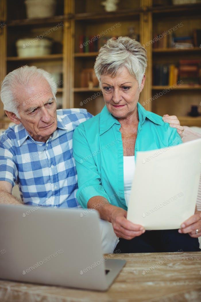 Senior couple checking bills in living room