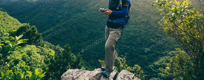 Hiker using smartphone  on forest mountain top cliff edge