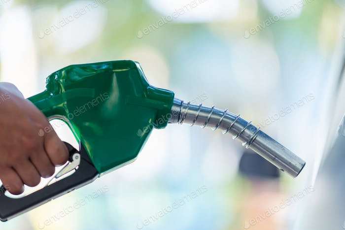 Man Handle pumping gasoline fuel nozzle to refuel. Vehicle fueling facility at petrol station
