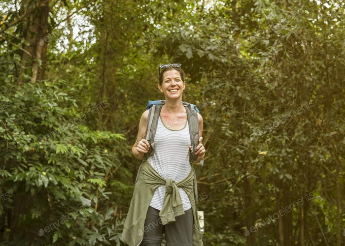Cheerful female backpacker in the forest