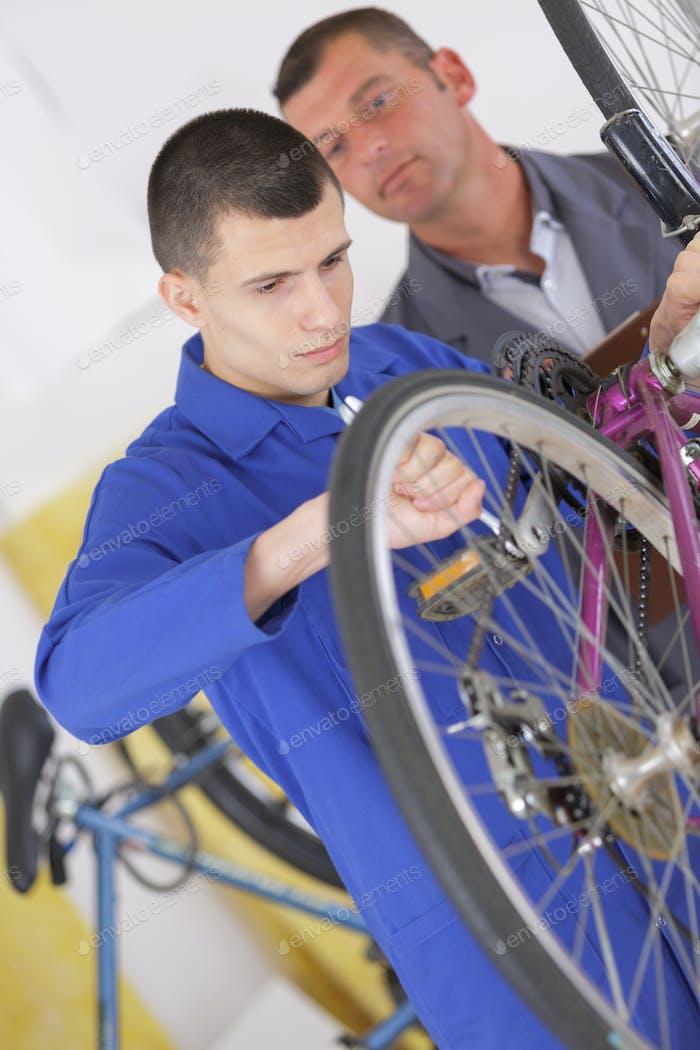 bicycle mechanic adjusting front derailleur mechanism on mountain bike