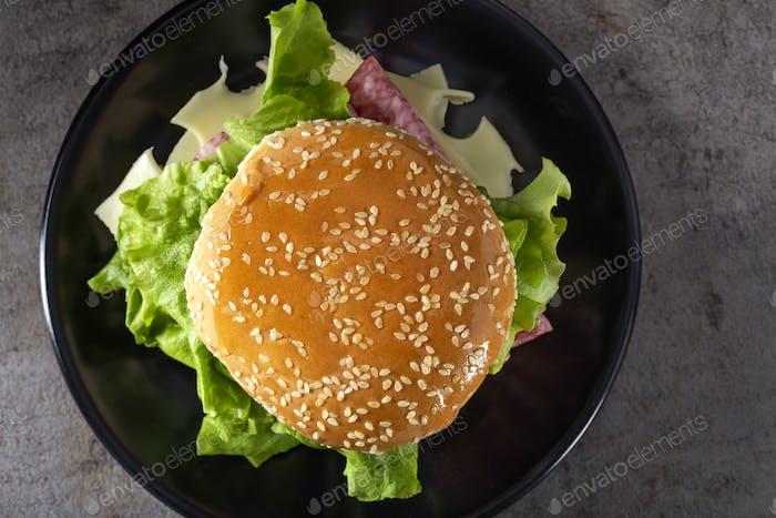 Ein Sandwich mit Salami, Käse, Tomaten und Saucen
