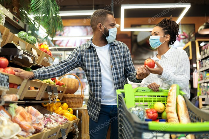 Couple In Masks Buying Vegetables Doing Grocery Shopping In Store
