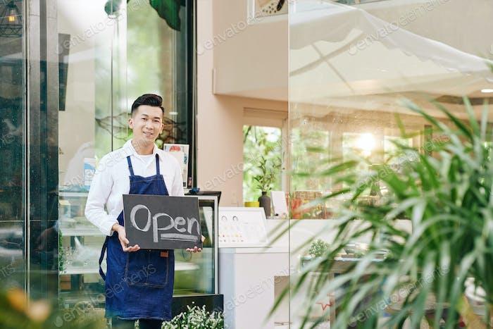 Waiter inviting customers