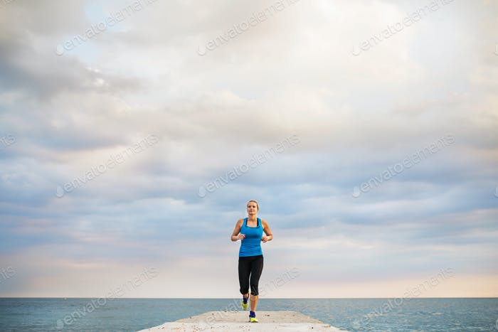 A young sporty woman running on a pier by the ocean outside.