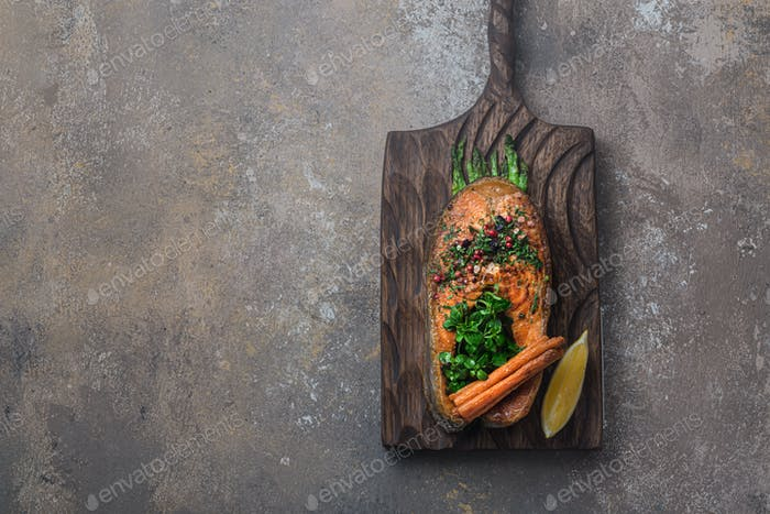 Fried salmon steak with vegetables on wooden board, flat lay copy space