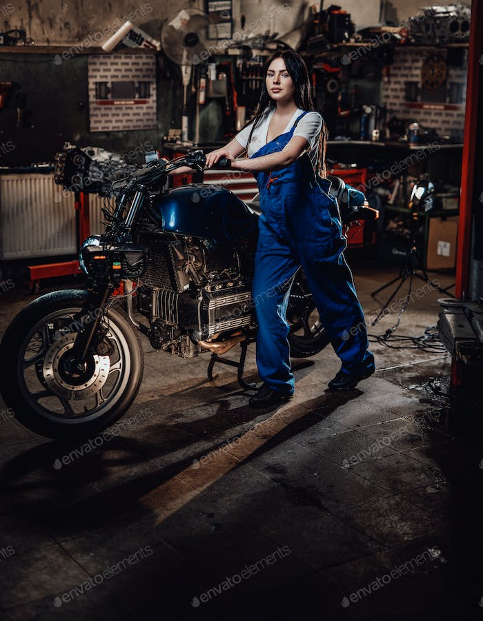 Beautiful young female mechanic in blue overalls posing with custom bobber in garage or workshop