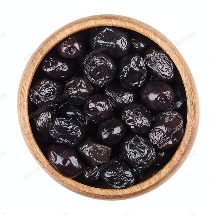 Black olives in a bowl on white background
