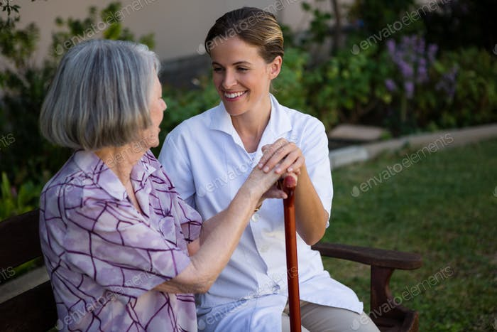 Woman talking to doctor while sitting on bench at park