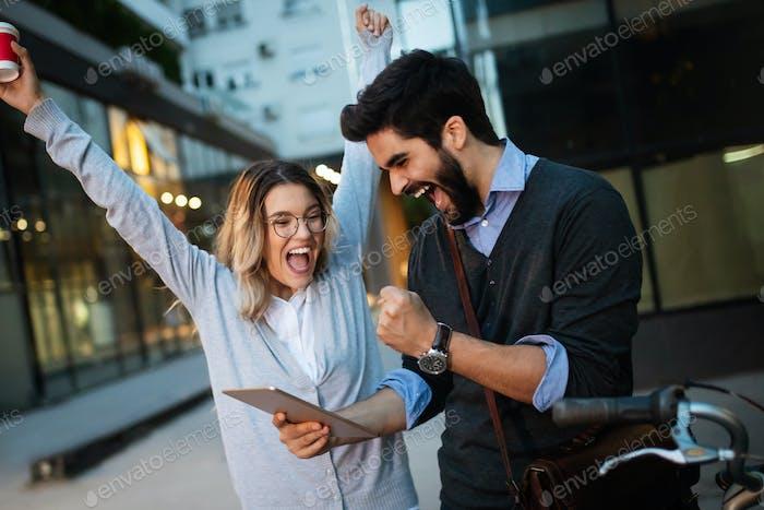 Emocionado joven pareja viendo contenido en una tableta outdoo