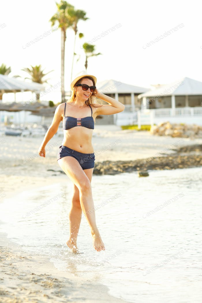 Woman in a hat and swimsuit walking on the beach on a hot summer