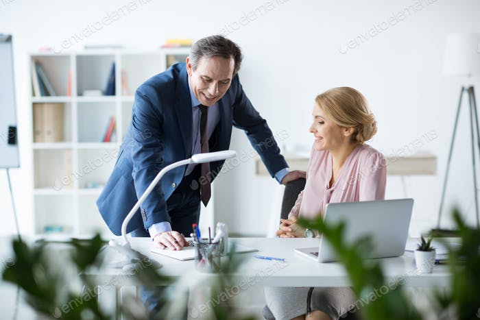 smiling business people doing paperwork in office