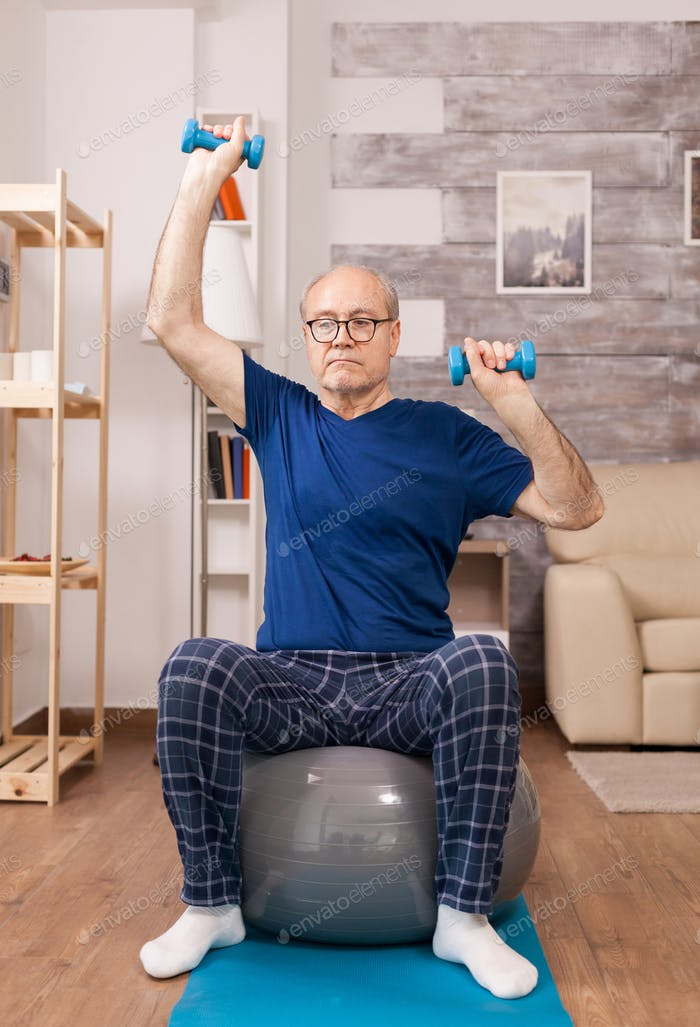 Elderly man doing sport in pajamas