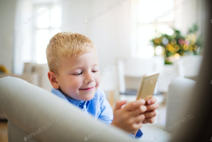 A small boy with smartphone sitting on an armchair at home at Christmas time.